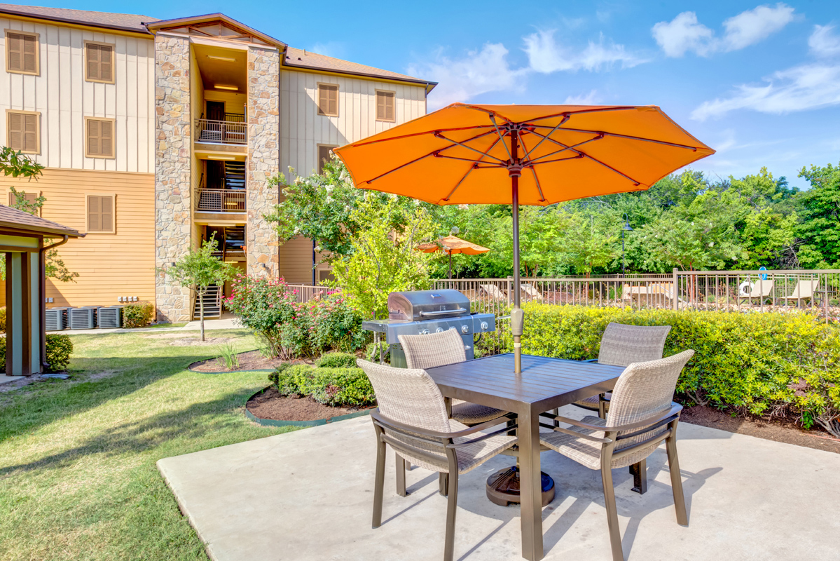 Outdoor BBQ Grill with umbrella-covered table seating, surrounded by lush landscape just outside pool fence