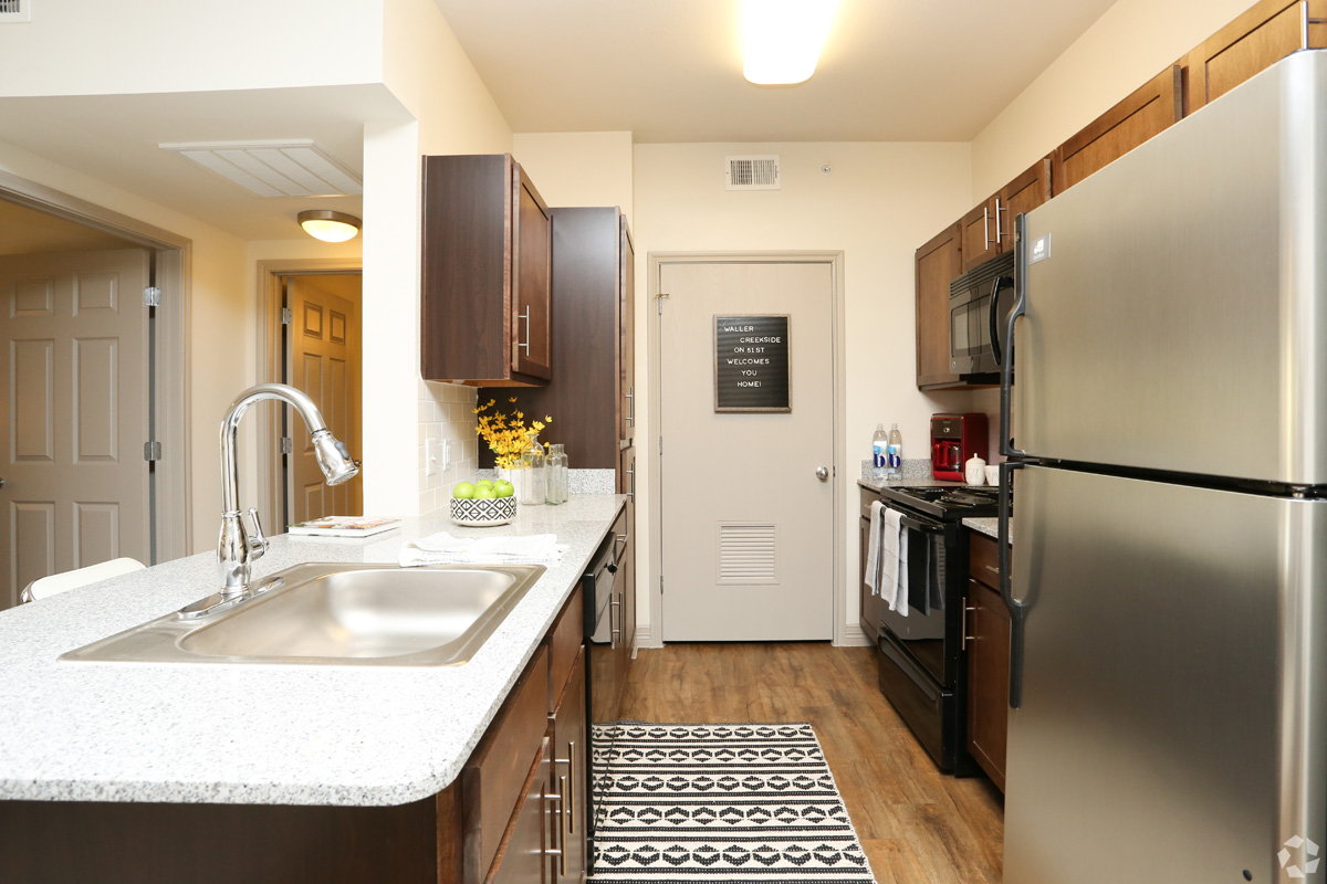 Model kitchen with stainless steel fridge, black microwave and stove, wood-style floors and granite countertops