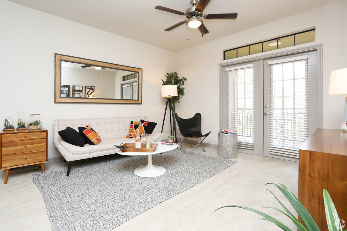 Model living room with plush carpeting, ceiling fan, cable ready, and access to patio/balcony door