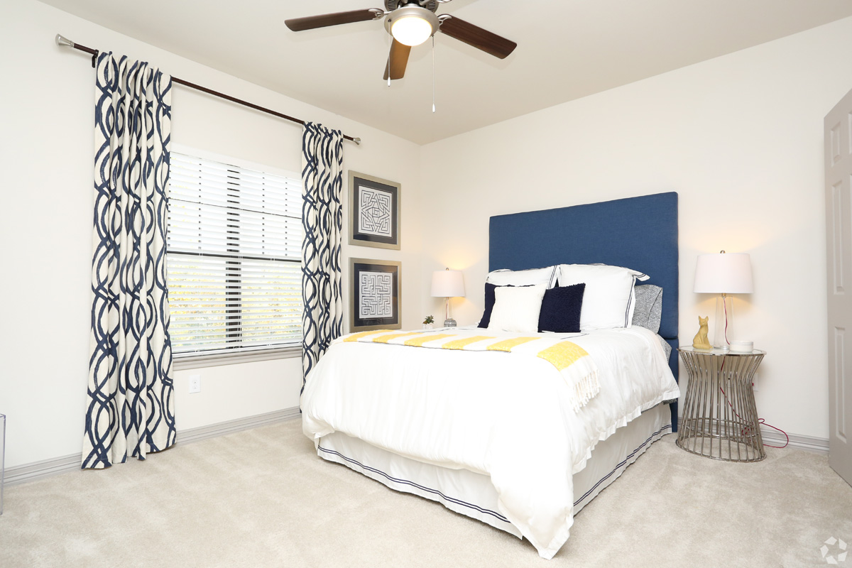 Model bedroom with large window, ceiling fan, and plush carpeting